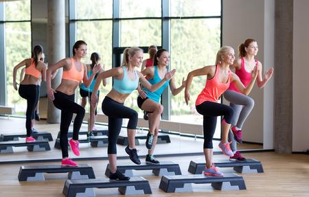 피트니스, 스포츠, 교육, 헬스 클럽 및 생활 양식 개념 - 체육관에서 스테퍼 함께 일하는 여성 그룹