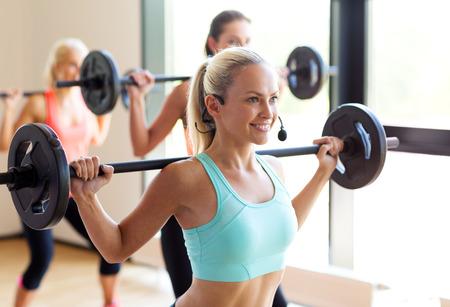 mujeres fitness: fitness, deporte, entrenamiento y estilo de vida concepto - grupo de mujeres con pesas en el gimnasio Foto de archivo