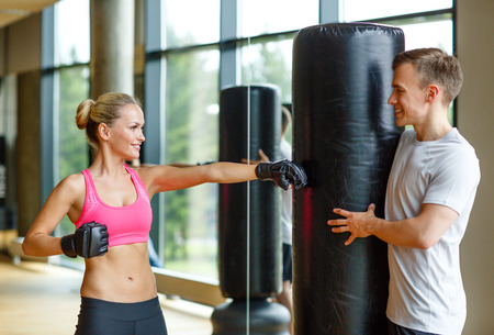 sport, fitness, lifestyle and people concept - smiling woman with personal trainer boxing in gym photo