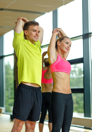 gym class: sport, fitness, lifestyle and people concept - smiling man and woman stretching in gym