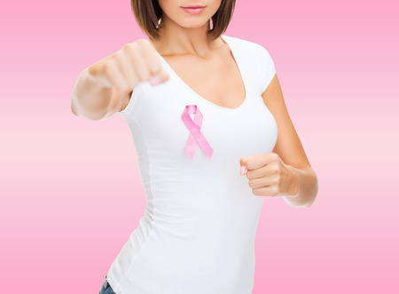 healthcare and medicine concept - close up smiling young woman in blank white t-shirt with pink breast cancer awareness ribbon fighting over pink background