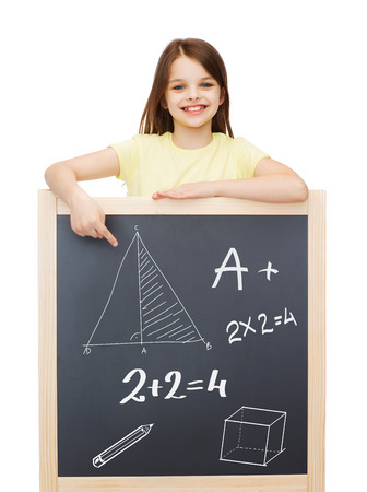 people, childhood and education concept - smiling little girl pointing finger to blackboard photo