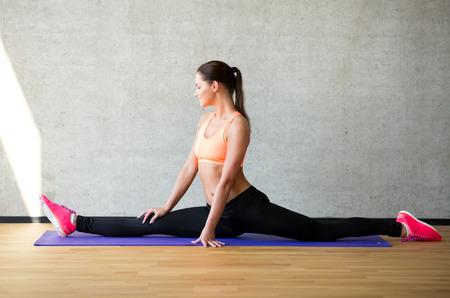 stretching: fitness, deporte, entrenamiento y estilo de vida concepto - mujer sonriente que se extiende la pierna sobre la colchoneta en el gimnasio