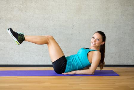 fitness, deporte, entrenamiento y estilo de vida concepto - sonriente mujer haciendo ejercicios en colchoneta en el gimnasio Foto de archivo