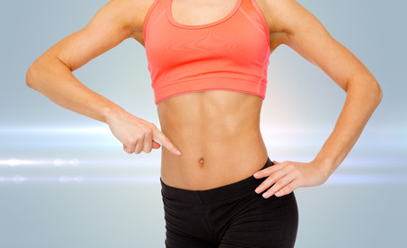 six persons: fitness, exercise and diet concept - close up of woman pointing finger at her six pack Stock Photo