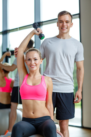 fit ball: fitness, sport, exercising and diet concept - smiling young woman and personal trainer with dumbbell in gym