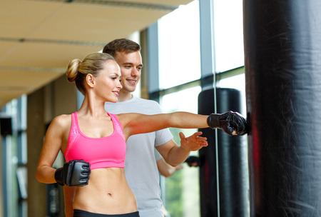 スポーツ、フィットネス、ライフ スタイル、人々 の概念 - 女性ボクシングのジムでパーソナル トレーナーに笑みを浮かべて