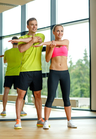 sport, fitness, lifestyle and people concept - smiling man and woman stretching in gym photo