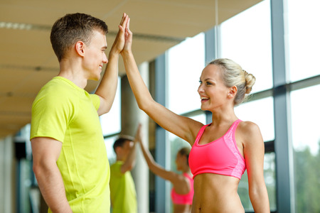 athletic wear: sport, fitness, lifestyle and people concept - smiling man and woman making high five in gym