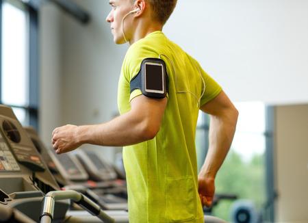 스마트 폰, 이어폰 체육관에서 러닝 머신에서 운동하는 남자 - 스포츠, 피트니스, 라이프 스타일, 기술과 사람들이 개념을