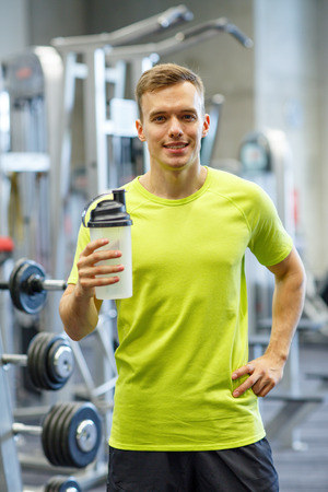 sport, fitness, lifestyle and people concept - smiling man with protein shake bottle in gym photo