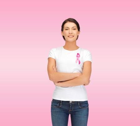 nice breast: healthcare, support, people and medicine concept - smiling woman in blank white t-shirt with breast cancer awareness ribbon over pink background Stock Photo