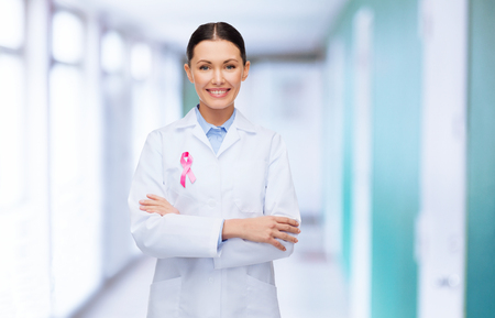 beautiful breasts: healthcare and medicine concept - smiling female doctor with pink cancer awareness ribbon over hospital background