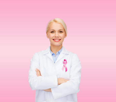 healthcare and medicine concept - smiling female doctor with pink cancer awareness ribbon over pink background photo