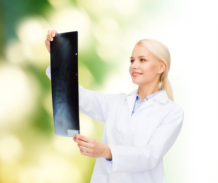 roentgenogram: healthcare, medicine and radiology concept - smiling female doctor looking at x-ray over natural background