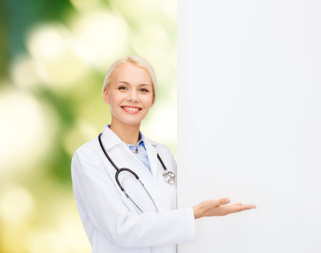 happy doctor woman: healthcare, advertisement, people and medicine concept - smiling female doctor with stethoscope showing something over natural background Stock Photo