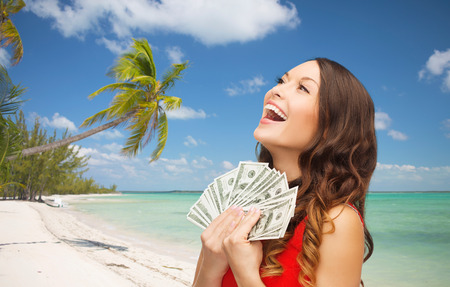 currency: christmas, x-mas, sale, banking and travel concept - smiling woman in red dress with us dollar money over tropical beach background