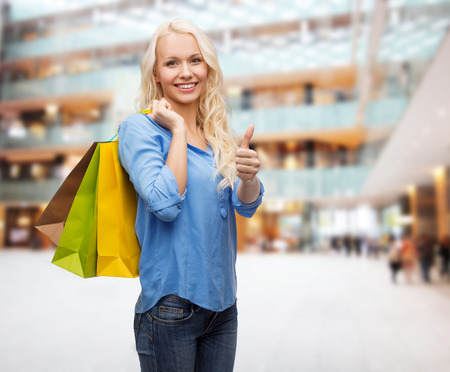 SATISFIED: retail, gesture and sale concept - smiling woman with many shopping bags showing thumbs up