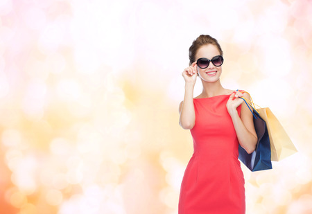fancy bag: shopping, sale, christmas and holiday concept - smiling elegant woman in red dress and sunglasses with shopping bags Stock Photo