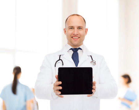 commercial medicine: medicine, advertisement and teamwork concept - smiling male doctor with stethoscope showing tablet pc computer screen over group of medics