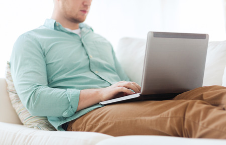 freelance: technology, home and lifestyle concept - close up of man working with laptop computer and sitting on sofa at home