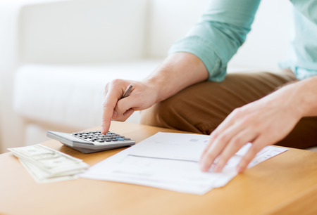 savings, finances, economy and home concept - close up of man with calculator counting money and making notes at home Imagens - 30746339