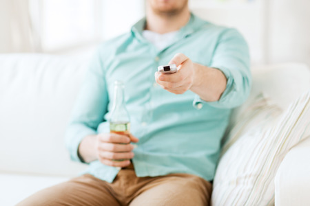 drinks, television, leisure and people concept - man changing tv channels and drinking beer at home photo