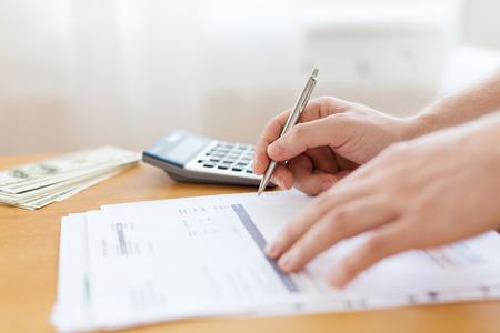 accountancy: savings, finances, economy and home concept - close up of man with calculator counting money and making notes at home