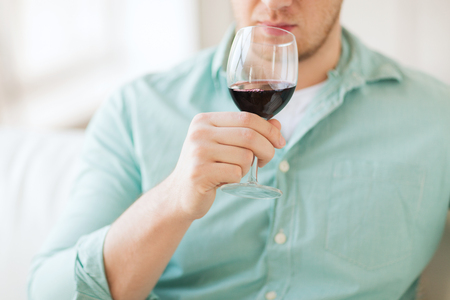 free time: drinks, relax, leisure and people concept - close up of man drinking red wine and sitting on couch at home