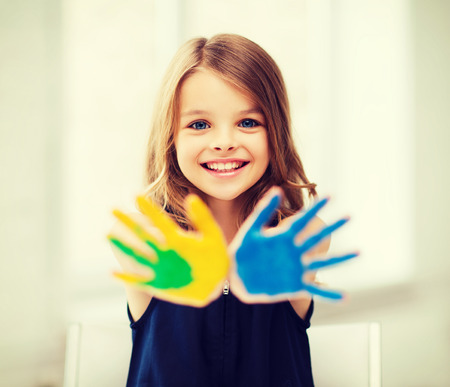 kids painted hands: education, school, art and painitng concept - little student girl showing painted hands at school