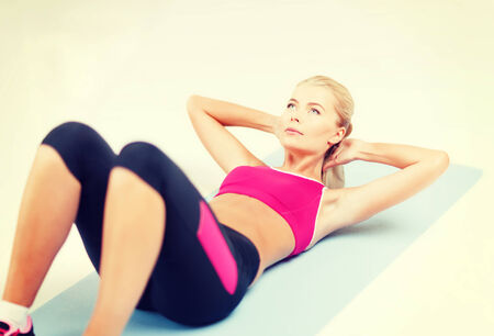 fitness and exercice concept - beautiful sporty woman doing exercise on the floor photo