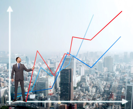 real estate growth: business, development and people concept - smiling man holding graph line over chart and cityscape background