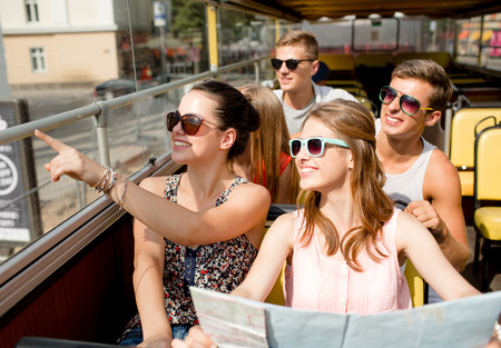 friendship, travel, vacation, summer and people concept - group of smiling friends with map traveling by tour bus