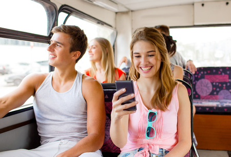 friendship, travel, summer vacation, technology and people concept - smiling couple with smartphone traveling by tour bus and making selfie photo