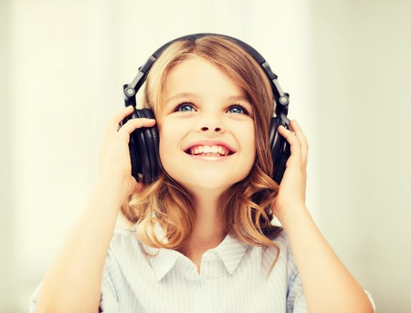 home audio: home, technology and music concept - little girl with headphones at home Stock Photo