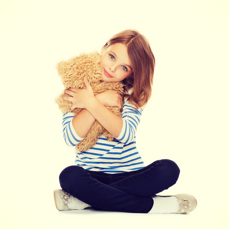 childhood, toys and shopping concept - cute little girl hugging teddy bear photo
