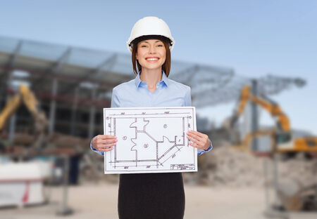 outline women: building, developing, construction and architecture concept - smiling businesswoman in white helmet showing blueprint