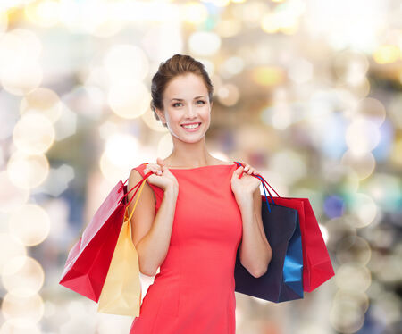 shopping, sale, christmas and holiday concept - smiling elegant woman in red dress with shopping bags
