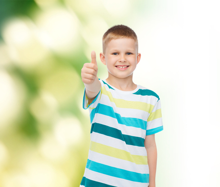 happiness, childhood, ecology and people concept - smiling little boy in casual clothes showing thumbs up over green background Stock Photo