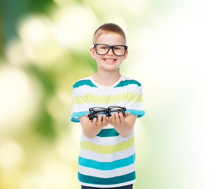 multiple choice: vision, health, ecology and people concept - smiling little boy in eyeglasses holding spectacles over green background Stock Photo