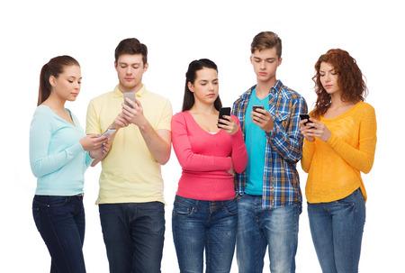 vriendschap, technologie en mensen concept - groep van ernstige tieners met smartphones