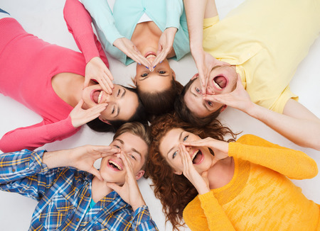 hispanic students: friendship, youth, gesture and people - group of smiling teenagers lying on floor in circle and shouting