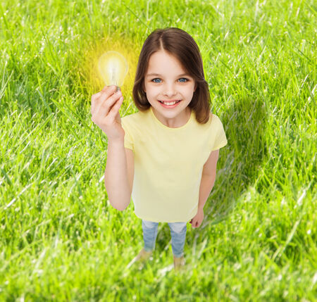 electricity, education and people concept - smiling little girl holding light bulb photo