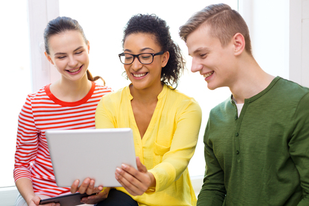 education, technology and internet concept - smiling students looking at tablet pc computer at school photo