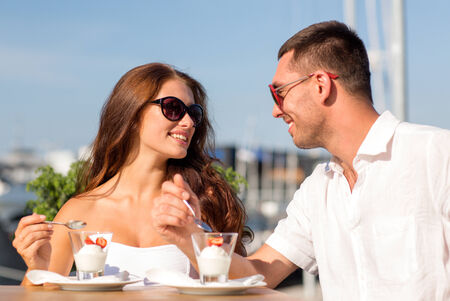 love, dating, people and food concept - smiling couple smiling couple wearing sunglasses eating dessert and looking to each other at cafe photo