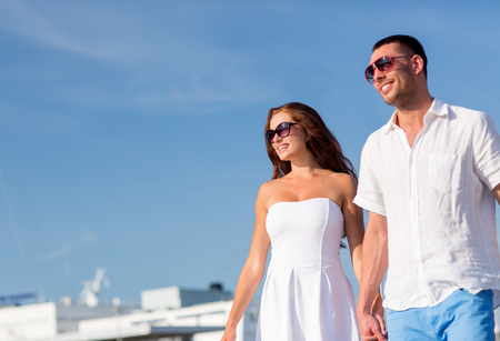 love, travel, tourism and people concept - smiling couple wearing sunglasses and walking in city photo