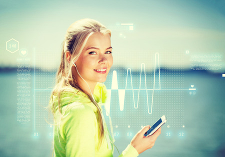 resting heart rate: fitness and lifestyle concept - woman doing sports and listening to music outdoors Stock Photo