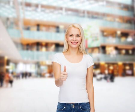 t-shirt design and happy people concept - woman in blank white t-shirt showing thumbs up photo