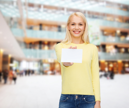 happiness and people concept - smiling young woman in casual clothes with white blank business or name card photo