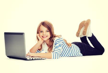niños jugando en la escuela: la educación, la tecnología y el concepto de Internet - una sonrisa de niña estudiante con ordenador portátil tirado en el suelo Foto de archivo
